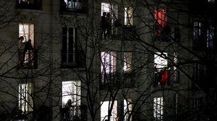 Des Parisiens applaudissent depuis leur balcon à 20h, le 18 mars 2020, en hommage aux soignants mobilisés dans la lutte contre le coronavirus. (THOMAS COEX / AFP)