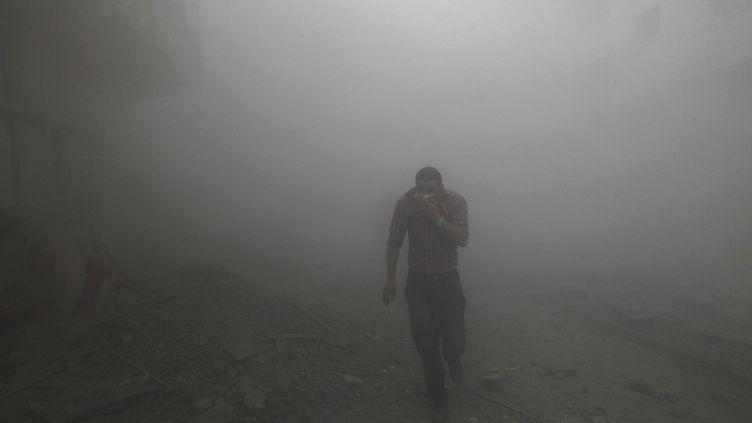Un homme court dans une rue touchée par des tirs de missiles, dans l'est de la Syrie, le 12 mars 2013. (REUTERS)