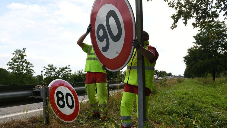 Les employés de la Direction interdépartementale des routes de l'Est remplacent un panneau de limitation à 90 km/h par un panneau 80 km/h, à Wittenheim (Haut-Rhin), le 29 juin 2018. (SEBASTIEN BOZON / AFP)