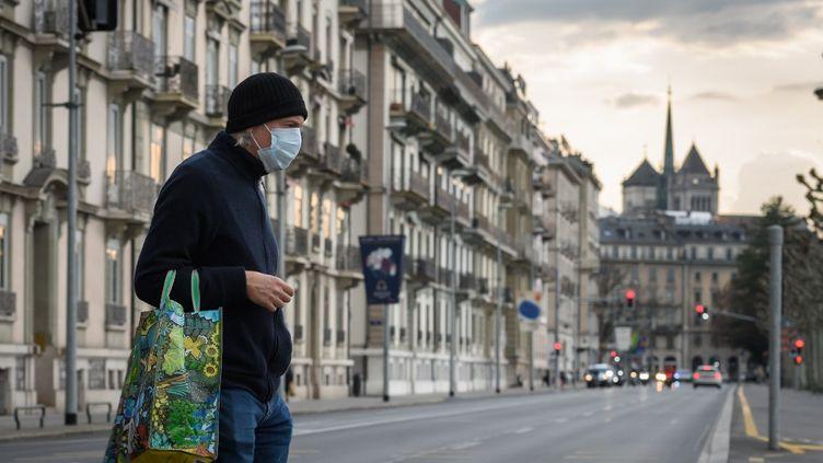 Un homme traverse une rue vide à Genève (Suisse), le 20 mars 2020. (FABRICE COFFRINI / AFP)
