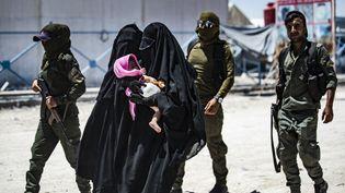 Une patrouille de sécurité escorte deux femmes soupçonnées d'être membres de l'Etat islamique, dans le camp al-Hol au nord de la Syrie, le 23 juillet 2019. (illustration) (DELIL SOULEIMAN / AFP)