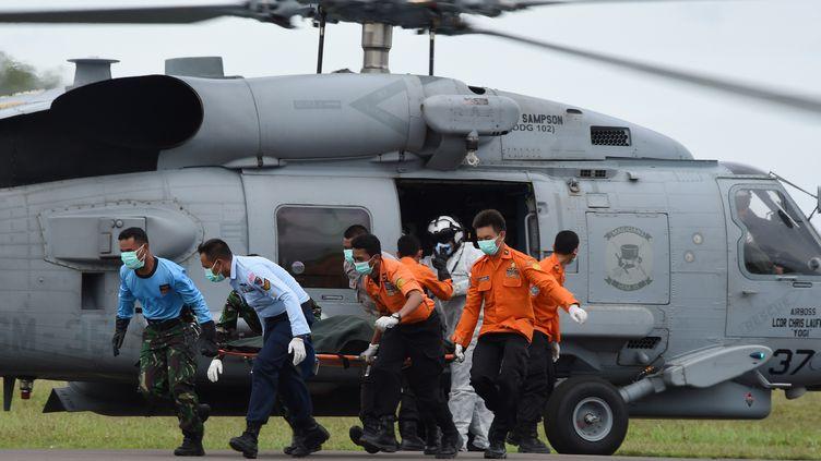Des membres des équipes de secours et de recherche indonésiennes ramènent à terre le corps d'une victime du vol d'AirAsia, le 2 janvier 2014, à la base militaire dePangkalan Bun (Indonésie). (ADEK BERRY / AFP)