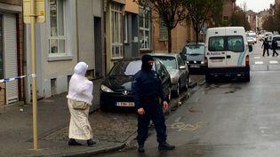 Une riveraine tente de rentrer chez elle, à Molenbeek (Bruxelles), juste après l'intervention policière, lundi 16 novembre 2015. (KOCILA MAKDECHE / FRANCETV INFO)