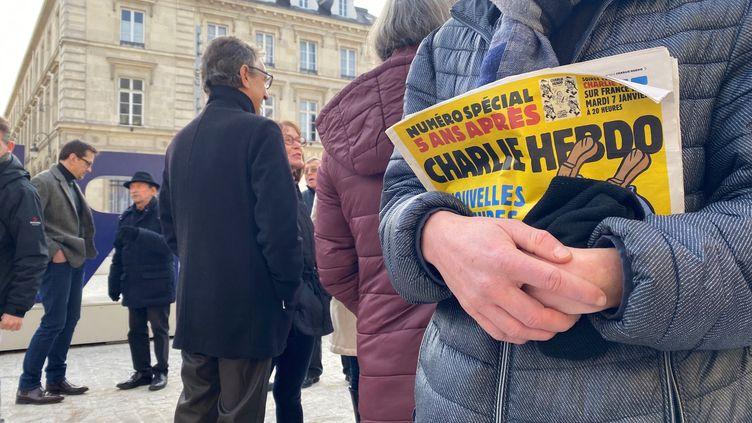 Un homme tenant le journal de Charlie Hebdo lors d'un rassemblement à Reims. (STÉPHANE MAGGIOLINI / FRANCE-BLEU CHAMPAGNE)