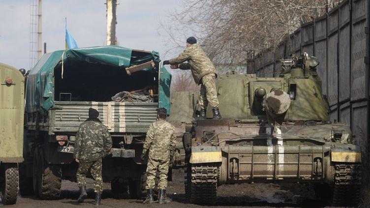 Des soldats ukrainiens charges des armes lourdes dans des camions, près de Donetsk, dans l'Est de l'Ukraine, vendredi 6 mars 2015. (VIKTOR KOSHKIN / ANADOLU AGENCY / AFP)