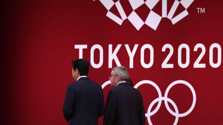 Le Premier ministre japonais, Shinzo Abe, aux côtés du président du CIO, Thomas Bach, le 24 juillet 2019, lors d'un événement organisé dans la capitale Tokyo. (BEHROUZ MEHRI / AFP)