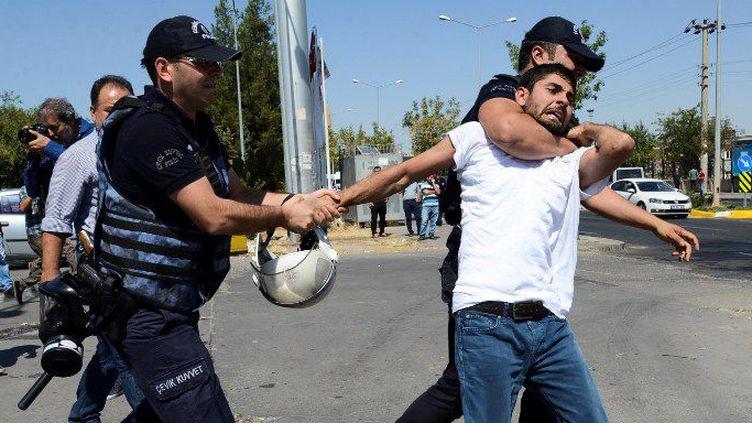 La police turque arrête un enseignant lors d'une manifestation à Diyarbakir, le 9 septembre 2016, pour protester contre la suspension de plus de 11.000 collègues soupçonnés de sympathies avec le PKK. (ILYAS AKENGIN/AFP)