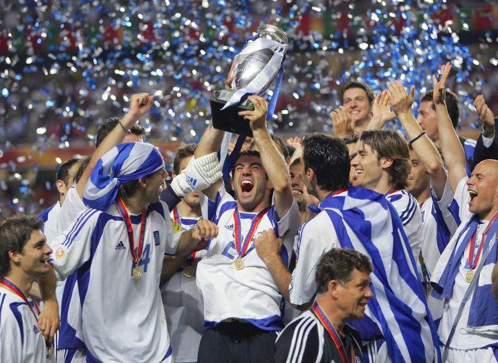 Georgios Karagounis et les Grecs soulèvent le trophée de l'Euro après leur victoire contre le Portugal, le 4 juillet 2004 à Lisbonne. (SORIANO/FIFE / AFP)