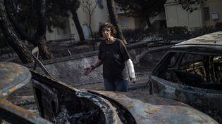 Une femme à Mati, en Grèce, après l'incendie violent et meurtrier, le 24 juillet 2018. (ANGELOS TZORTZINIS / AFP)