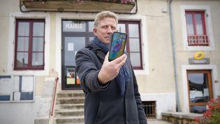 Jean-Sébastien Halliez, maire de Brassy (Nièvre), constate le faible réseau mobilesur la place du village. (PIERRE-LOUIS CARON / FRANCEINFO)