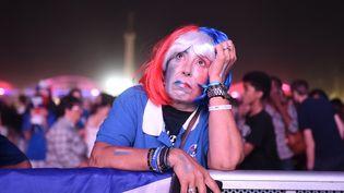 """Une supportrice française a bien du mal à cacher son désarroi après la défaite des Bleus en finale de l'Euro, dans la """"fan zone"""" de Bordeaux, le 10 juillet 2016. (NICOLAS TUCAT / AFP)"""