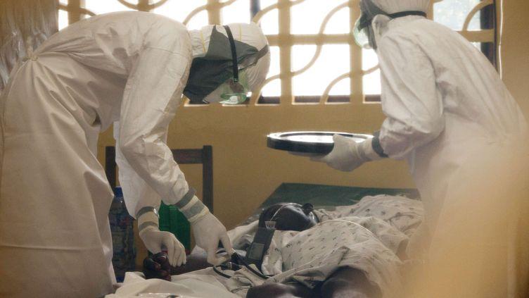 Le docteur Kent Brantly, ici à gauche, traite un patient contaminé par le virus Ebola à Monrovia (Liberia), en 2014. (SIPA / AP)