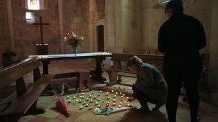 Une femme allume des bougies à la mémoire des victimes de l'accident de Puisseguin, le 24 octobre 2015 àPetit-Palais-et-Cornemps (Gironde). (THIBAULT CAMUS / AP / SIPA)