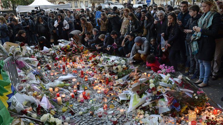 Des anonymes rendant hommage aux victimes des attaques du13 novembre, près du Bataclan, le 15 novembre 2015 à Paris. (MIGUEL MEDINA / AFP)