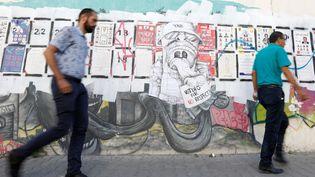 Des piétons passent, le 1er octobre 2019, près d'affiches pour les élections législatives à Tunis. (REUTERS - ZOUBEIR SOUISSI / X02856)