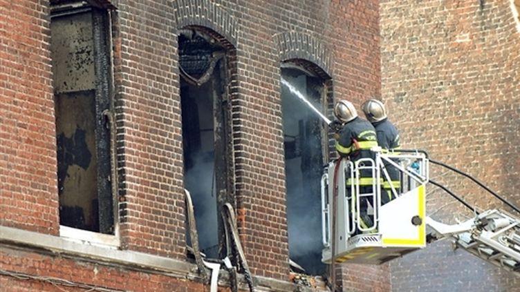 Les pompiers finissent d'éteindre un incendie dans une maison de Tourcoing (Nord), le 10 février 2010 (AFP / Philippe Huguen)