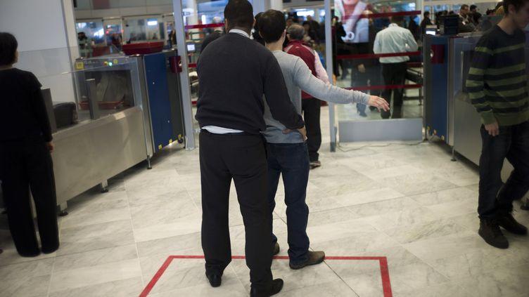 Un agent de sécurité procède à une palpation de sécurité, le 31 décembre 2012, à l'aéroport Roissy-Charles-de-Gaulle (Val-d'Oise). (FRED DUFOUR / AFP)