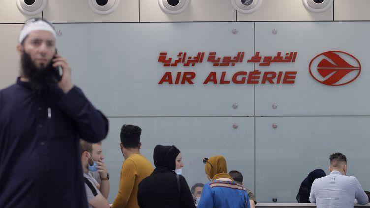Des voyageurs attendent d'enregistrer pour un vol pour Paris au comptoir d'Air Algérie, à l'aéroport d'Alger, le 1er juin 2021. (- / AFP)