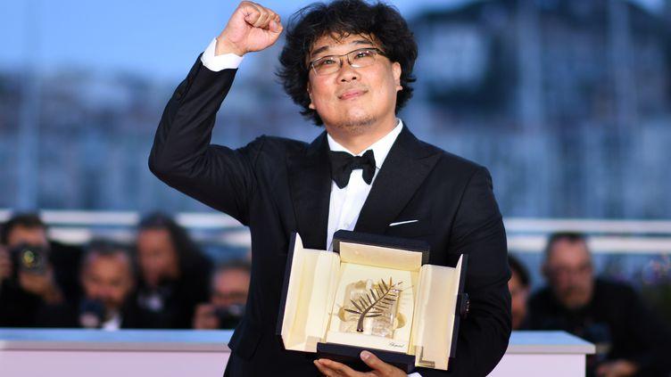 Le cinéaste Bong Joon-Ho peut brandir le poing... C'est la première fois qu'une Palme d'or est attribuée à un sud-coréen. Son nouveau film, Parasite, est à découvrir en salles dès le 5 juin 2019. (LOIC VENANCE / AFP)