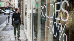 Une femme regarde la vitrine d'une boutique pendant les soldes d'été le 27 juin 2016 à Paris. (MAXPPP)