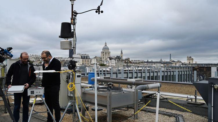 Des chercheurs duLaboratoire des sciences du climat et de l'environnement installent des capteurs de C02 sur la plateforme Qualair sur le toit de l'université de Jussieu, à Paris, le 20 octobre 2019. (DOMINIQUE FAGET / AFP)