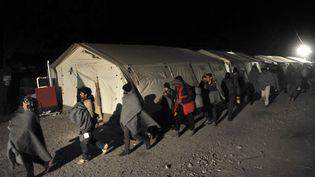 Des migrants traversant la frontière entre la Macédoine et la Grèce, le 9 décembre 2015. (SAKIS MITROLIDIS / AFP)