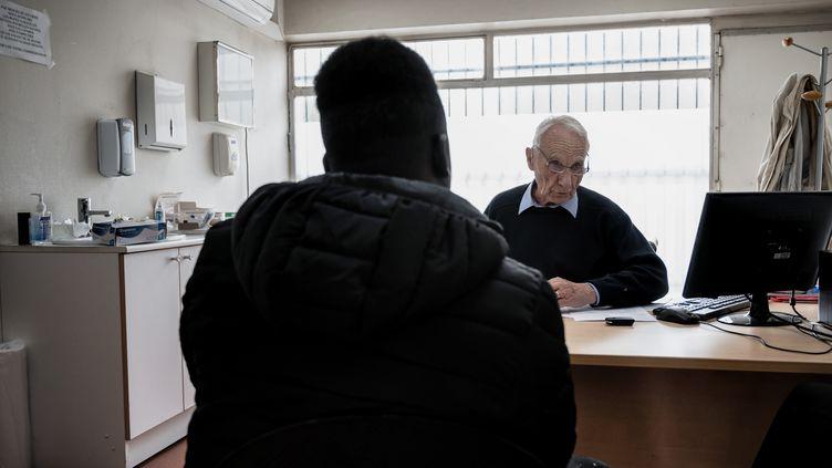 Un médecin membre de l'Association Médecine et Droit d'Asile avec un réfugié, à Lyon, le 2 avril 2019. (JEFF PACHOUD / AFP)