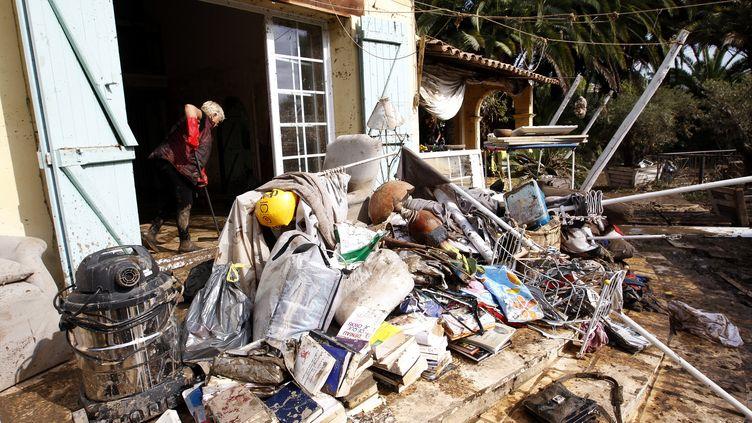 Une femme nettoie sa maison dévastée par les inondations à Biot (Alpes-Maritimes) le 6 octobre 2015. (JEAN CHRISTOPHE MAGNENET / AFP)