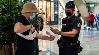 Un policier contrôle le pass sanitaire d'un client dans le centre commercial de La Part-Dieu, à Lyon (Rhône), le 18 août 2021. (NICOLAS LIPONNE / HANS LUCAS / AFP)