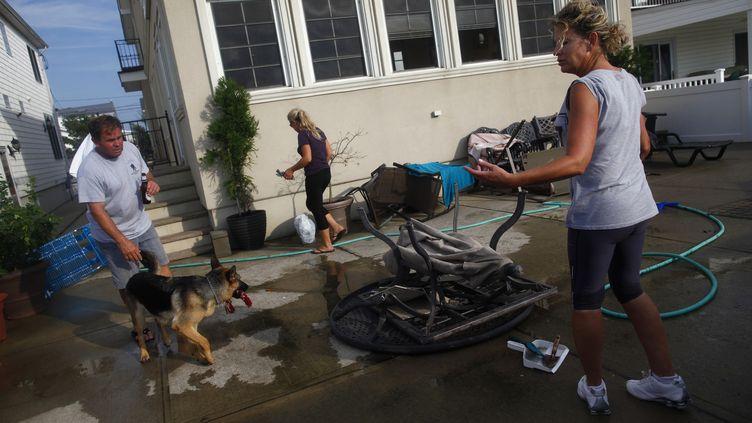 Des habitants de Breezy Point dans l'état deNew York nettoient les dégâts après le passage d'une tornade samedi 8 septembre 2012 (ERIC THAYER / REUTERS)