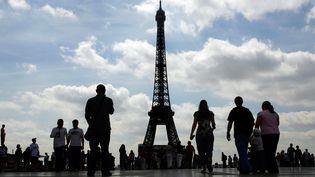 Des touristes admirent la tour Eiffel, le 13 juillet 2007 à Paris. (CLEMENS BILAN / AFP)