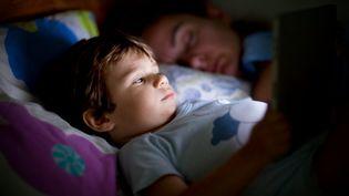 Un enfant se servant d'une tablette dans son lit. (THANASIS ZOVOILIS / FLICKR / GETTY IMAGES)