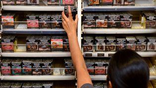 Une buraliste range des paquets neutres de cigarettes, le 1er décembre 2012, à Sydney (Australie). (WILLIAM WEST / AFP)