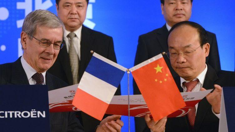 Philippe Varin, ancien patron de PSA Peugeot Citroën, signe un contrat avec Xu Ping, président de Dongfeng MotorGroup, à Pékin (Chine), le 28 mars 2014. (GOH CHAI HIN / AFP)