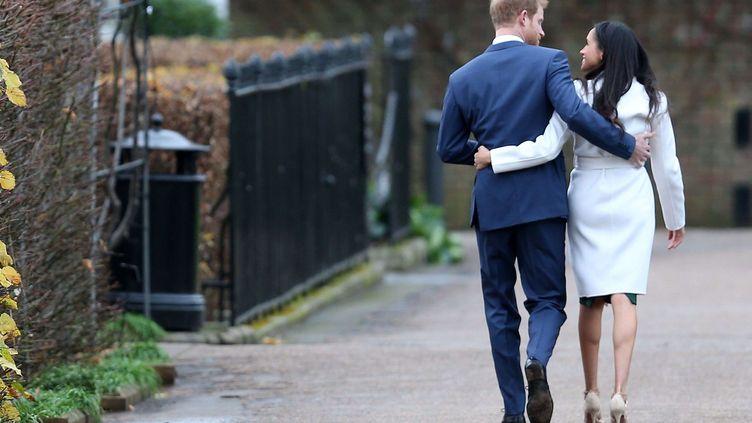 Le prince Harry et Meghan Markle s'éloignent des journalistes, après avoir annoncé leurs fiançailles, le 27 novembre 2017, au palais de Kensington (Royaume-Uni). (BERETTA /SIMS / SHUTTERSTOCK / SIPA)