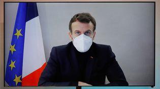 Emmanuel Macron, en visioconférence depuis son lieu de confinement, lors d'une table ronde pour la Conférence nationale humanitaire, le 17 décembre 2020. (CHARLES PLATIAU / POOL / AFP)