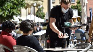Un serveur dans un café à Perpignan, en mai 2021 (illustration). (RAYMOND ROIG / AFP)