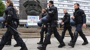 Des policiers marchent devant la statue de Karl-Marx à Chemnitz (Allemagne), le 1er septembre 2018, en marge des deux manifestationsde militants d'extrême droite et de gauche. (RALF HIRSCHBERGER / DPA)