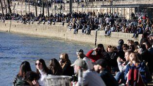 Des Parisiens prennent un bain de soleil le 27 février 2021 sur les quais de Seine. (THOMAS COEX / AFP)