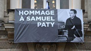 Un portrait de l'enseignant français Samuel Paty est affiché sur la façade de l'Opéra Comédie à Montpellier, le 21 octobre 2020, lors d'un hommage national à l'enseignant. (PASCAL GUYOT / AFP)