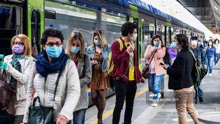 Des voyageurs sur un quai de la gare de Milan-Carona (Italie), le 4 mai 2020. (MIGUEL MEDINA / AFP)