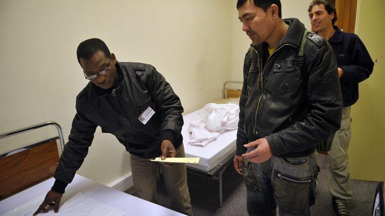 Un bénévole de l'Association Emmaüs installe des demandeurs d'asile dansun centre d'hébergement, le 21 décembre 2010 à Paris. (BERTRAND LANGLOIS / AFP)