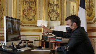 Le président de la République, Emmanuel Macron, échange par visioconférence avec des collégiens des Alpes-de-Haute-Provence, mardi 6 avril 2021 depuis le palais de l'Elysée à Paris. (CHRISTOPHE ENA / AFP)