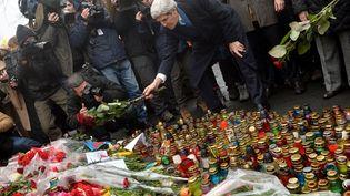 Le secrétaire d'Etat américain John Kerry dépose une rose au mémorial des victimes des affrontements à Kiev (Ukraine), le 4 mars 2014. (SERGEI SUPINSKY / AFP)