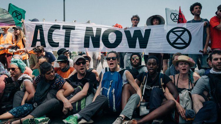 Des militants d'Extinction Rebellion bloquent le pont de Sully, à Paris, le 28 juin 2019. (MATHIAS ZWICK / HANS LUCAS / AFP)