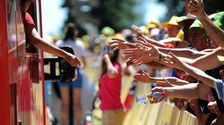 Une hôtesse distribue des cadeaux dans la caravane publicitaire du Tour de France, le17 juillet 2016 à Bourg-en-Bresse (Ain). (MAXPPP)