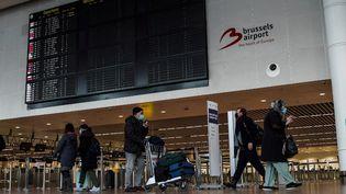 Des passagers dans le hall des départs de l'aéroport de Bruxelles (Belgique), le 20 janvier 2021. (LOIS DENIS / HANS LUCAS / AFP)