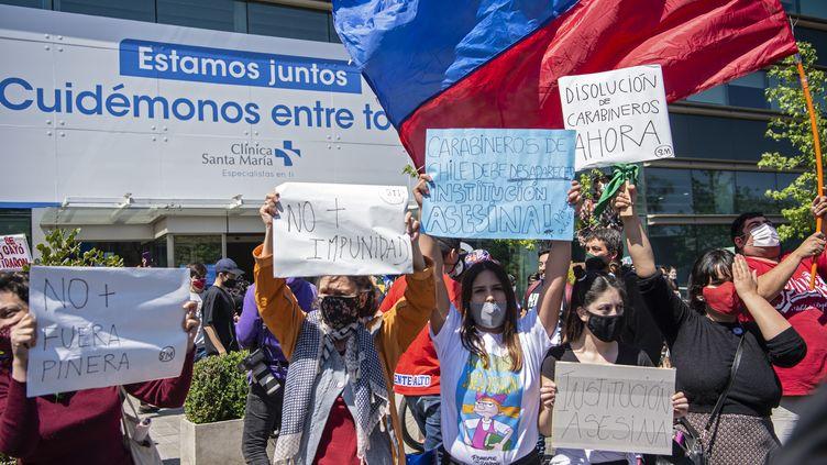 Le 3 octobre 2020 au Chili à Santiago, des manifestantes protestent contre les violences policières devant la clinique où un adolescent de 16 ans est hospitalisé après avoir été jeté d'un pont par un policier lors d'une manifestation. (MARTIN BERNETTI / AFP)