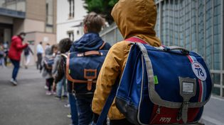 Des élèves attendent avant de rentrer en classe, le 12 mai 2020, à Paris. (PHILIPPE LOPEZ / AFP)
