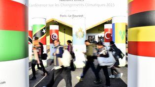 Des visiteurs passent devant l'entrée du centre de conférences accueillant la COP21, le 3 décembre 2015, au Bourget. (LOIC VENANCE / AFP)